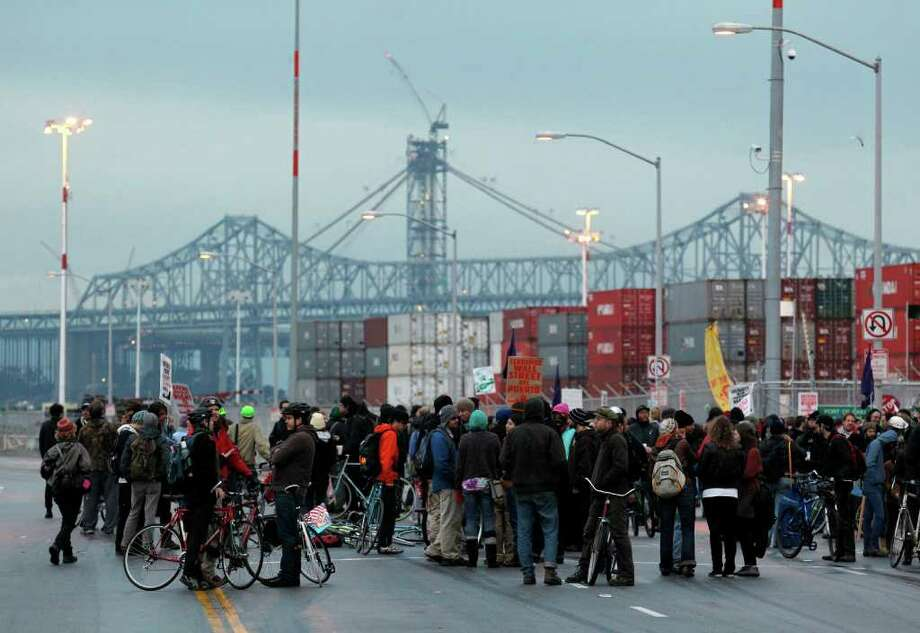 The San Francisco-Oakland Bay Bridge is seen in the background as protesters block one of the entrances to the Port of Oakland, Monday, Dec. 12, 2011, in Oakland, Calif. Anti-Wall Street protesters along the West Coast joined an effort Monday to blockade some of the nation's busiest docks, with the idea that if they cut off the ports, they cut into corporate profits.   (AP Photo/Beck Diefenbach) Photo: Beck Diefenbach