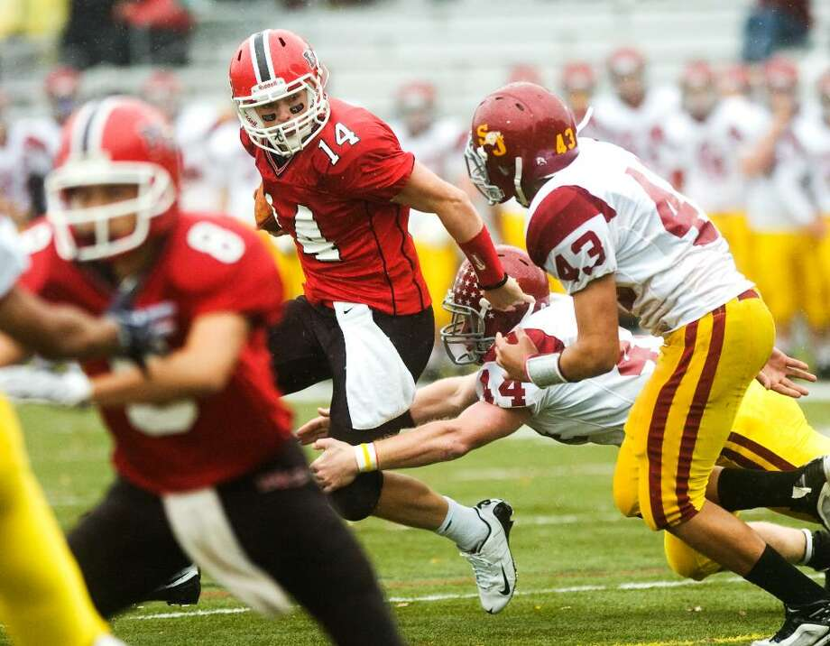 New Canaan High School's #14 Turner Baty, center, runs with the ball as he's pursued by St. Joseph's #14 Tyler Matakevich and #43 Sean Chinova during a football game at New Canaan. Photo: Kerry Sherck / Stamford Advocate Freelance