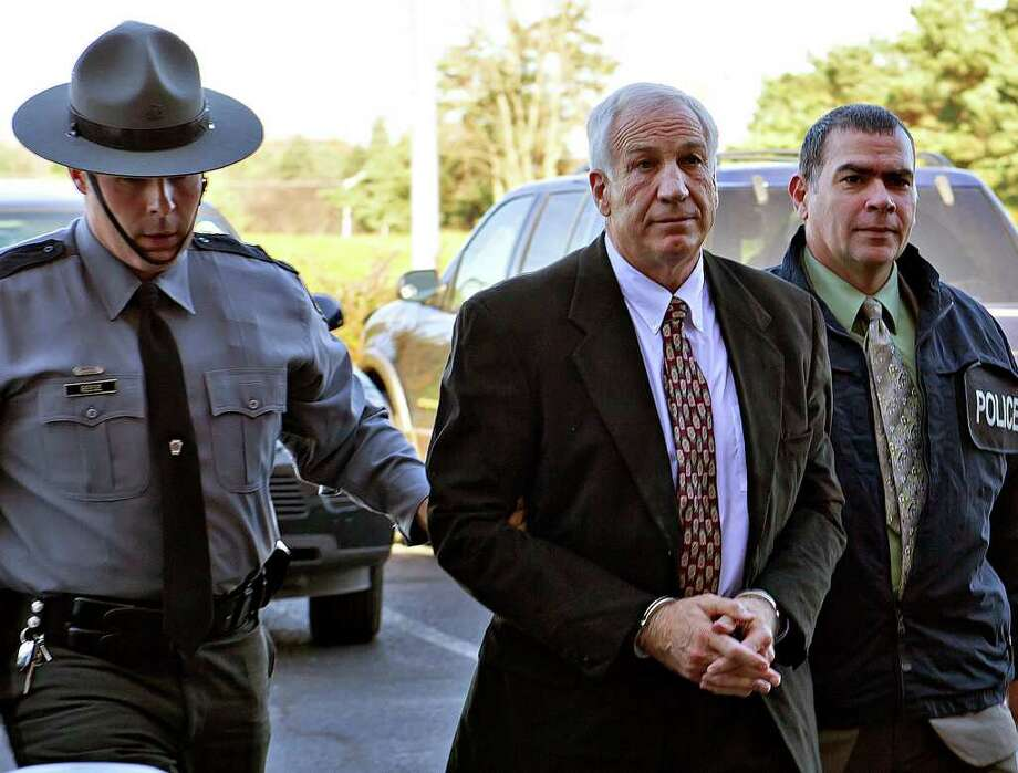 FILE - A Nov. 5, 2011 file photo shows former Penn State football defensive coordinator Jerry Sandusky, center, wearing handcuffs as he is escorted to the office of Centre County Magisterial District Judge Leslie A. Dutchcot, in State College, Pa.  Sandusky is charged with more than 50 counts related to sexual abuse over a 12-year period.  (AP Photo/The Patriot-News, Andy Colwell, File) Photo: Andy Colwell / 2011 AP