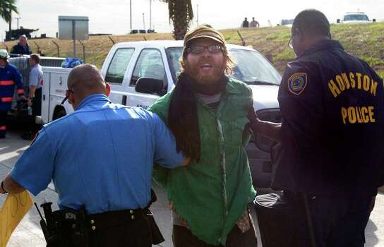 An Occupy Houston protestor is arrested after laying in the exit ramp of Loop 610 at the Port of Houston Authority Monday, Dec. 12, 2011, in Houston. Photo: Cody Duty, Houston Chronicle / © 2011 Houston Chronicle