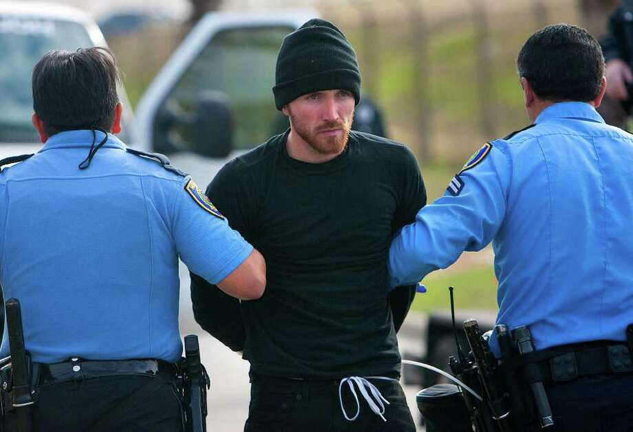 An Occupy Houston protestor is arrested after laying in the exit ramp of Loop 610 at the Port of Houston Authority Monday, Dec. 12, 2011, in Houston. The event, Occupy The Port, was part of a nationwide movement targeting the nation's ports. About 20 of the more than 100 protestors were arrested according to the Houston Police Department. Photo: Cody Duty, Houston Chronicle / © 2011 Houston Chronicle