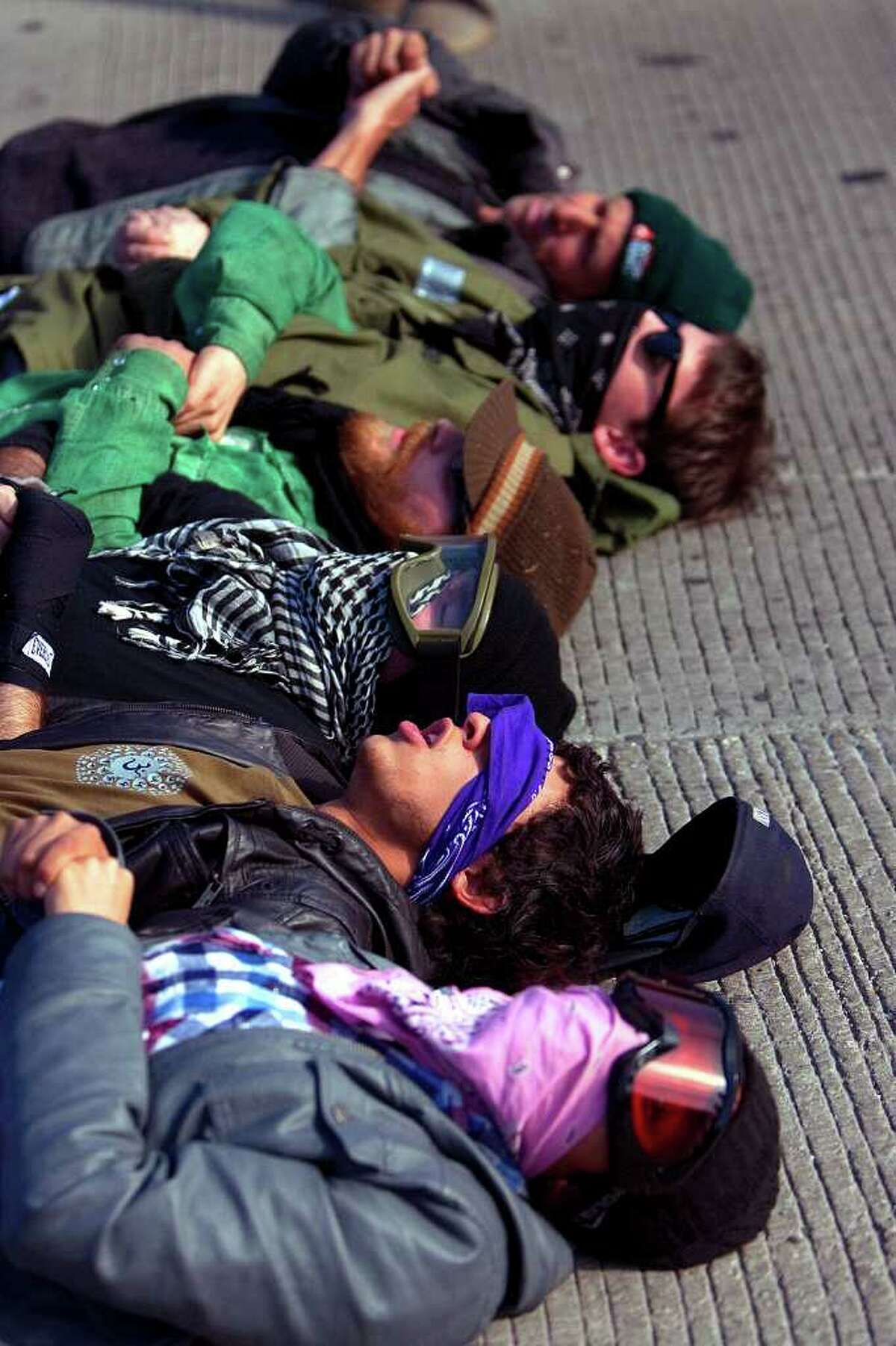 Occupy Houston protestors lay in the exit ramp of Loop 610 at the Port of Houston Authority Monday, Dec. 12, 2011, in Houston.