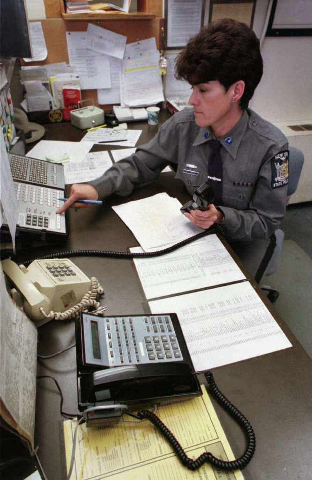 Times Union Staff Photo by Jonathan Fickies -- New York State Trooper Maureen Tuffey answers calls at the front desk at Troop G Headquarters in Loudonville Friday October 6, 1998. Capital Region 911 calls made from cellular phones come through on the black phone at bottom, and two others like it in the office.