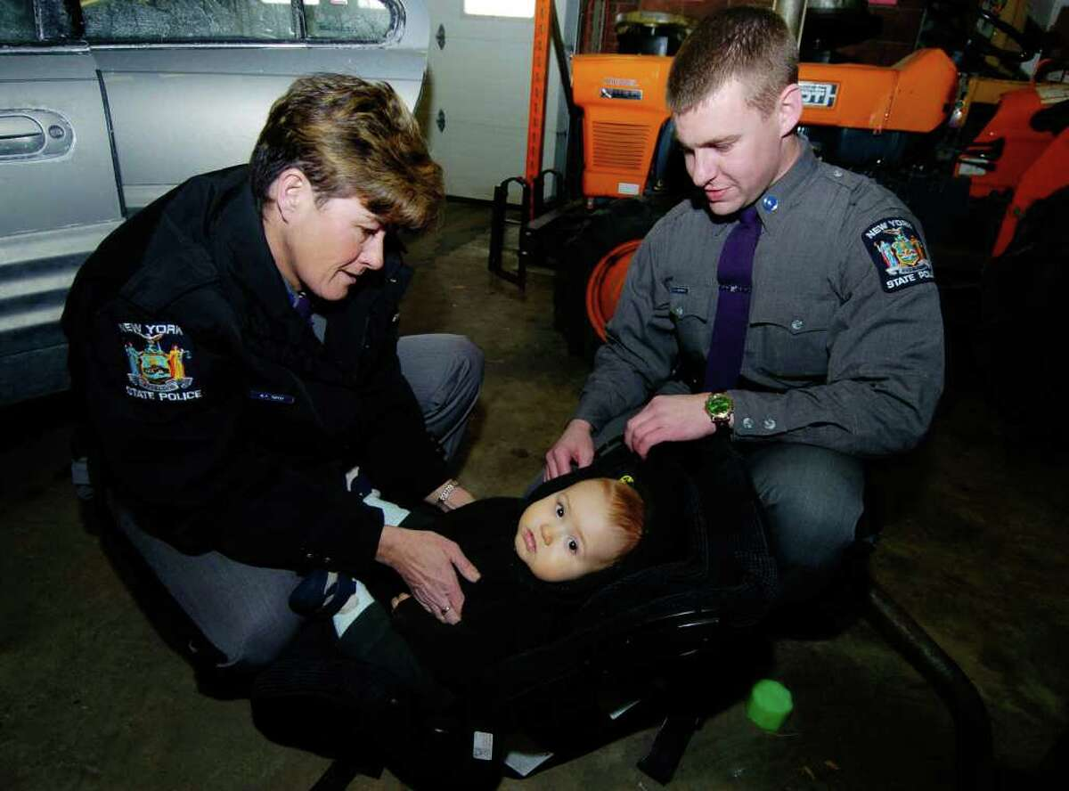 State troopers Maureen Tuffey and Doug Wildermuth discuss child safety seats in this 2004 file photo. The baby in the child seat is Benjamin Gadireault. Tuffey, one of the first four women to be appointed to the job, in 1973, is retiring Friday. (Skip Dickstein / Times Union archive)