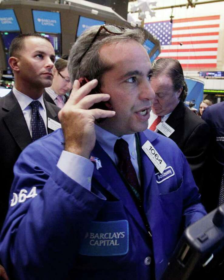 In this Dec. 9, 2011 photo, trader Anthony Satriale, center, works on the floor of the New York Stock Exchange. Enthusiasm for riskier assets such as stocks and the euro faded Monday, Dec. 12, 2011, as investors worried that Europe's new pact aimed at fixing the continent's debt crisis would be insufficient.  (AP Photo/Richard Drew) Photo: Richard Drew
