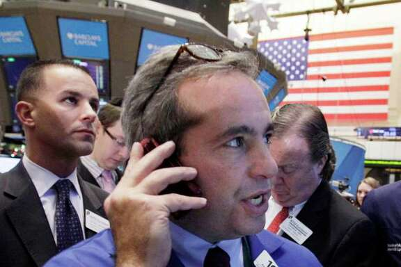 In this Dec. 9, 2011 photo, trader Anthony Satriale, center, works on the floor of the New York Stock Exchange. Enthusiasm for riskier assets such as stocks and the euro faded Monday, Dec. 12, 2011, as investors worried that Europe's new pact aimed at fixing the continent's debt crisis would be insufficient.  (AP Photo/Richard Drew)