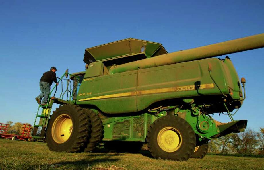In this photo taken Oct. 31, 2011, central Illinois farmer Dale Hadden climbs onto a combine on the family farm near Jacksonville, Ill. Hadden's farming operation is doing especially well this year for any of a number of reasons and will use this as an opportunity to funnel some of these profits into new machinery and paying off some land. (AP Photo/Seth Perlman) Photo: Seth Perlman