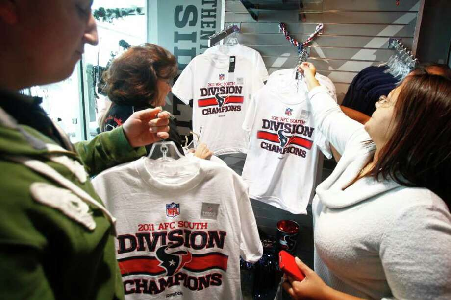 Michael Paulsen : Houston Chronicle ON DISPLAY: Andrew Russell, left, and his aunt Barbara Russell look through a display of AFC South Division Champions shirts on Monday at the Go Texan Store at Reliant Stadium.  MORE ON THE TEXANS ON PAGE C1; FIND MORE PHOTOS AT CHRON.COM Photo: Michael Paulsen / © 2011 Houston Chronicle