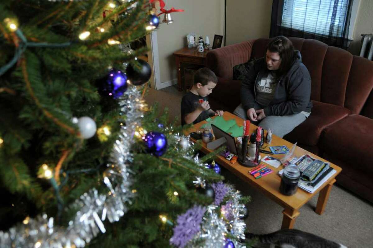 6 year old son Aaron Wright and his mother Nikki Dober were in a car accident on Saturday, and Aaron climbed out and helped direct emergency crews to the scene afterwards. They are making a Christmas decoration for his school class, as they relax in the living room of their home on Monday Dec. 12, 2011 in East Berne, N.Y. (Philip Kamrass / Times Union )