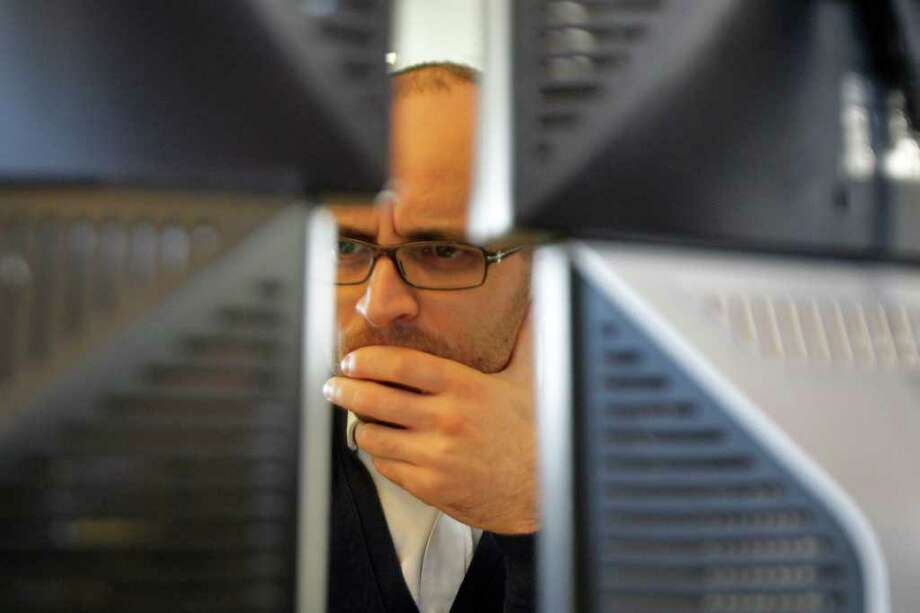 Michel Euler : aSSOCIATED PRESS LOOKING FOR SHELTER: A trader, seen Monday between screens in a bank in Paris, scans market figures as investors worried that Europe's new pact on debt would be insufficient. Photo: Michel Euler / AP