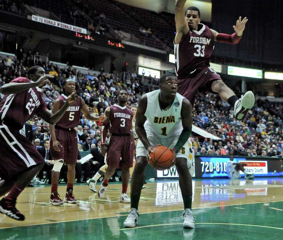 Fordham's Chris Gaston leaps over Siena's OD Anosike during the first half of Siena's 74-59 loss at the Times Union Center on Monday night Dec. 12, 2011 in Albany, N.Y.    (Philip Kamrass / Times Union ) Photo: Philip Kamrass / 00015373D