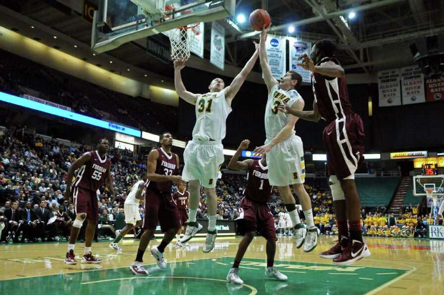 Siena's Owen Wignot, left, and Kyle Downey, right, go up for a rebound while surrounded by Fordham d
