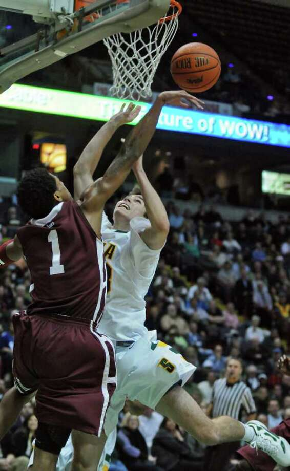 Fordham's Branden Frazier blocks a shot by Siena's Rob Poole, right, during the second half of Siena's 74-59 loss to Fordham at the Times Union Center on Monday night Dec. 12, 2011 in Albany, N.Y.    (Philip Kamrass / Times Union ) Photo: Philip Kamrass / 00015373D