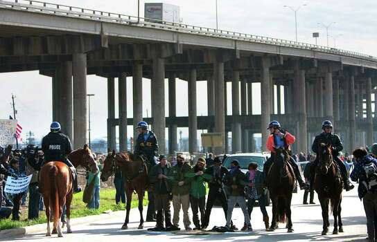 Occupy Houston protestors stand in protest in the exit ramp of Loop 610 at the Port of Houston Authority Monday, Dec. 12, 2011, in Houston. The event, Occupy The Port, was part of a nationwide movement targeting the nation's ports. Around 20 members were arrested according to the Houston Police Department. (Cody Duty / Houston Chronicle) Photo: Cody Duty / © 2011 Houston Chronicle