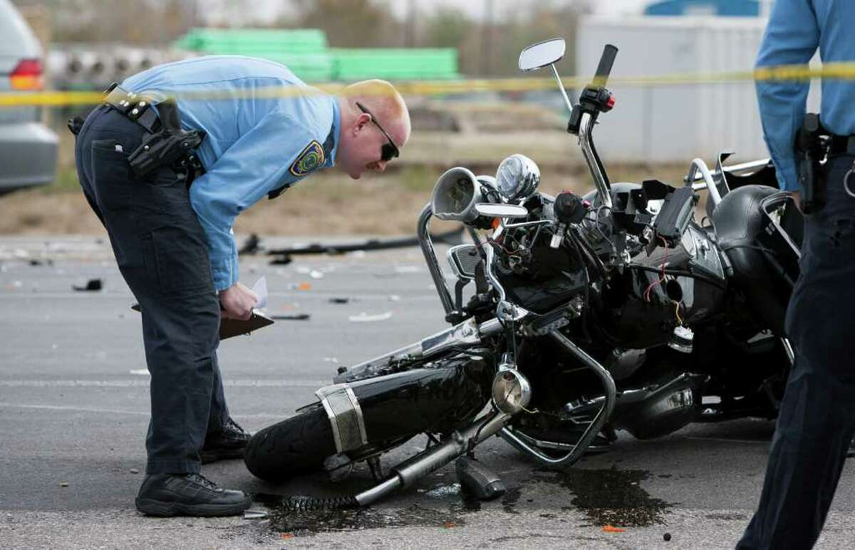 ANDREW RICHARDSON : CHRONICLE ACCIDENT: A Houston police officer inspects the motorcycle of Pasadena police Sgt. Matt Novotny, who was injured escorting a funeral procession on Dec. 12.