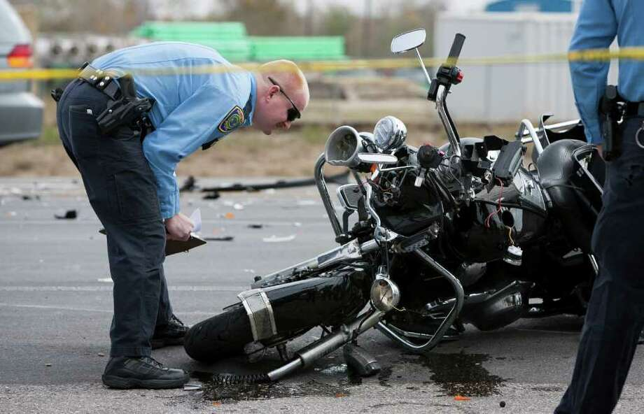 ANDREW RICHARDSON : CHRONICLE ACCIDENT: A Houston police officer inspects the motorcycle of Pasadena police Sgt. Matt Novotny, who was injured escorting a funeral procession on Dec. 12. Photo: Andrew Richardson / © 2011 Houston Chronicle