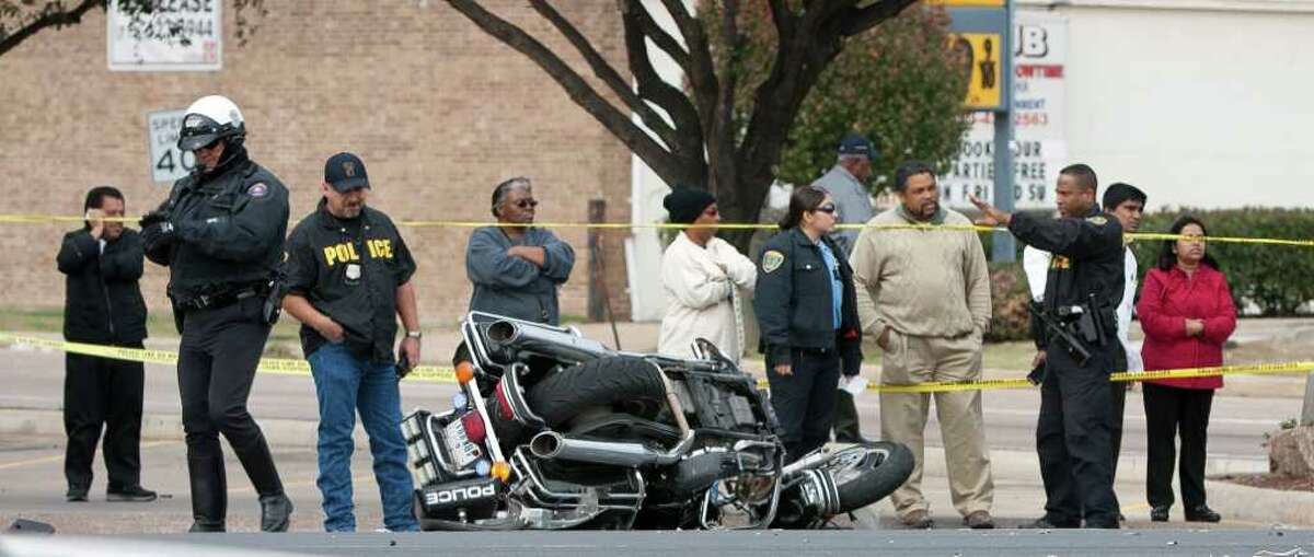 """Officers secure the crash scene at the intersection of Almeda Rd. and Fuqua St. on Monday, Dec. 12, 2011, in Houston. Sgt. George """"Matt"""" Novotny, a 32 year veteran of the Pasadena Police Department, was escorting a funeral procession and had come to a stop on his motorcycle in the center of the intersection when he was struck by woman driving a blue Honda CRV. The Honda collided with a second vehicle and came to a halt. Novotny was transported from the scene to Memorial Hermann Hospital via Life Flight helicopter, he was conscious and alert. The other two drivers did not sustain injuries. ( Andrew Richardson / Houston Chronicle )"""