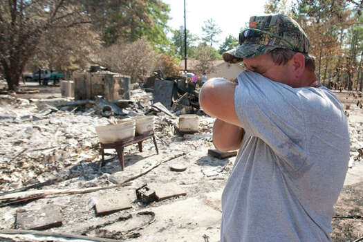 Rocky Barr wipes away a tear as he surveys the remains of his home on Sanders Cemetery Road in Magnolia, Texas on Monday, Sept. 12, 2011.   Fed by howling winds whipped up by the remnants of Tropical Storm Lee, flames streaked across drought-stricken Texas, where more than 190 fires statewide have killed four people. The worst damage was in Bastrop, where two smaller fires joined to form a monster blaze that has destroyed more than 1,550 homes and charred more than 34,000 acres.  (AP Photo/The Courier, Karl Anderson) Photo: Karl Anderson, Associated Press / AP