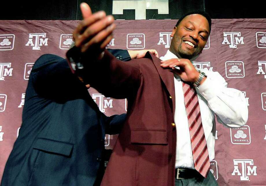DAVE McDERMAND: ASSOCIATED PRESS MAROON MOMENT: Newly appointed Texas A&M football coach Kevin Sumlin, right, is outfitted in his team's colors Monday. Photo: Dave McDermand / Bryan-College Station Eagle