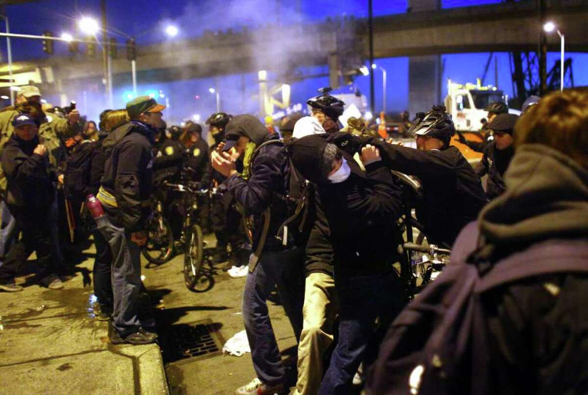 Police scuffle with protesters after deploying two flash-bang grenades on Monday, December 12, 2011 at the Port of Seattle. Hundreds of anti-Wall Street protesters gathered at the port and tried to shut down operations. Protesters scuffled with police during the rally and police used pepper spray and two flash-bang grenades to disperse the crowd after a protester threw a lit road flare toward officers. Another threw red paint on officers.