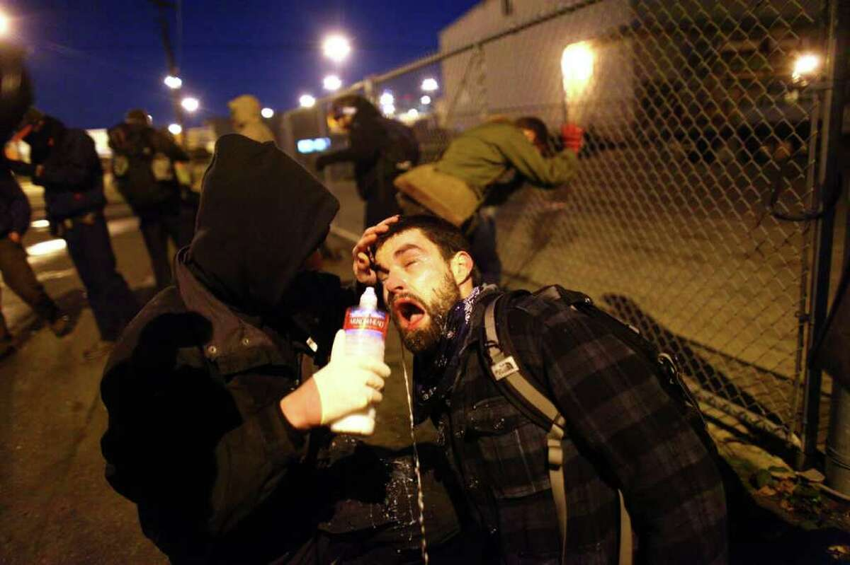 An Occupy Seattle protester has liquid poured on his face to ease the pain after Seattle Police used pepper spray on protesters on Monday, December 12, 2011 at the Port of Seattle. Hundreds of anti-Wall Street protesters gathered at the port and tried to shut down operations. Protesters scuffled with police during the rally and police used pepper spray and two flash-bang grenades to disperse the crowd after a protester threw a lit road flare toward officers. Another threw red paint on officers.