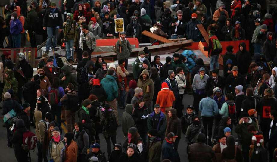 Protesters man a barricade blocking entry to the Port of Seattle on Monday, December 12, 2011 at the Port of Seattle. Hundreds of anti-Wall Street protesters gathered at the port and tried to shut down operations. Protesters scuffled with police during the rally and police used pepper spray and two flash-bang grenades to disperse the crowd after a protester threw a lit road flare toward officers. Another threw red paint on officers. Photo: JOSHUA TRUJILLO / SEATTLEPI.COM