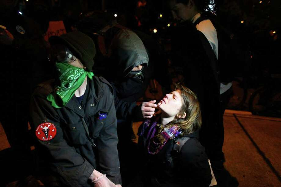 An injured protester is assisted on Monday, December 12, 2011 at the Port of Seattle. Hundreds of anti-Wall Street protesters gathered at the port and tried to shut down operations. Protesters scuffled with police during the rally and police used pepper spray and two flash-bang grenades to disperse the crowd after a protester threw a lit road flare toward officers. Another threw red paint on officers. Photo: JOSHUA TRUJILLO / SEATTLEPI.COM