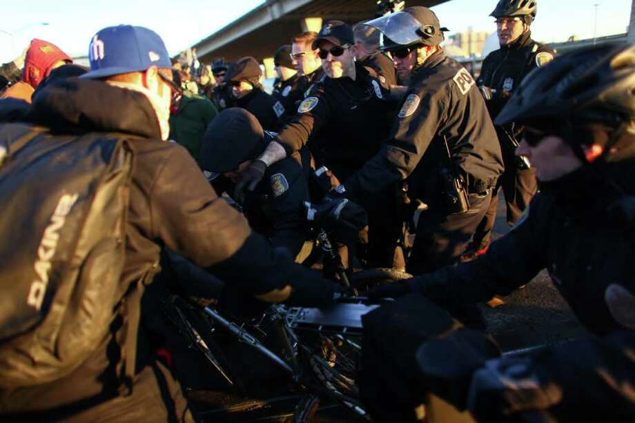 Police and Occupy Seattle protesters clash on Monday, December 12, 2011 at the Port of Seattle. Officers were trying to clear the protesters from the street. Hundreds of anti-Wall Street protesters gathered at the port and tried to shut down operations. Protesters scuffled with police during the rally and police used pepper spray and two flash-bang grenades to disperse the crowd after a protester threw a lit road flare toward officers. Another threw red paint on officers. Photo: JOSHUA TRUJILLO / SEATTLEPI.COM