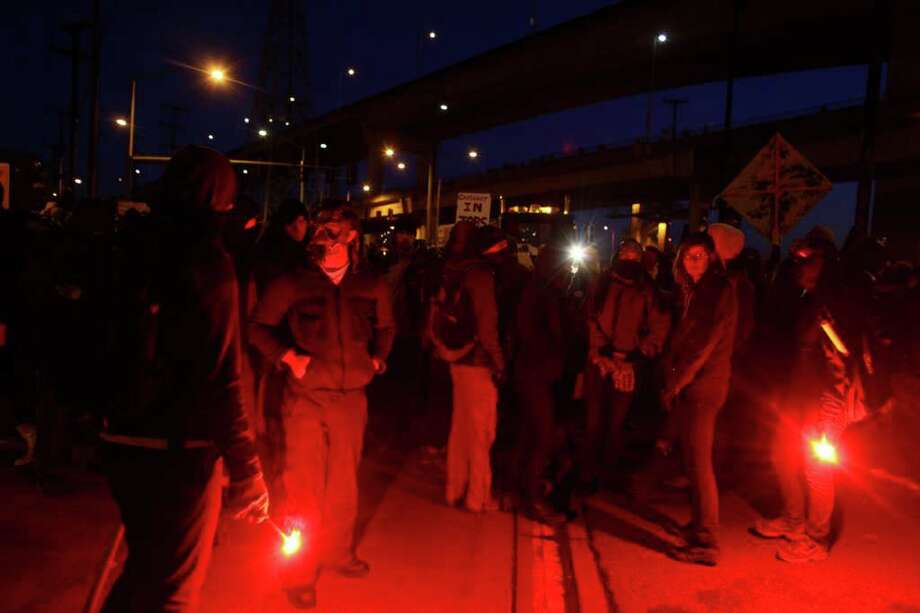 Protesters with road flares man a barricade blocking entry to the Port of Seattle on Monday, December 12, 2011 at the Port of Seattle. Hundreds of anti-Wall Street protesters gathered at the port and tried to shut down operations. Protesters scuffled with police during the rally and police used pepper spray and two flash-bang grenades to disperse the crowd after a protester threw a lit road flare toward officers. Another threw red paint on officers. Photo: JOSHUA TRUJILLO / SEATTLEPI.COM