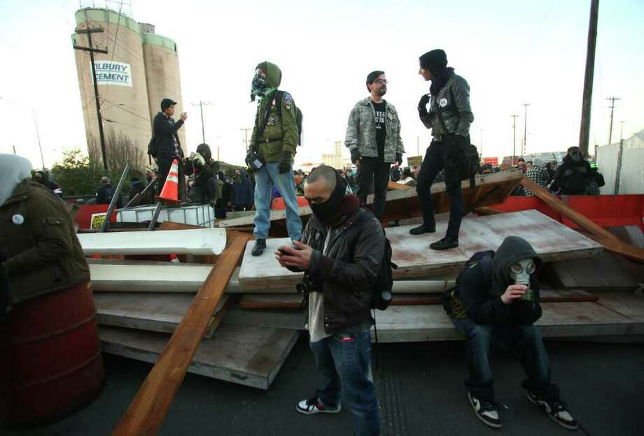 Protesters wait for police to arrive after they constructed a barricade on Monday, December 12, 2011 at the Port of Seattle. Hundreds of anti-Wall Street protesters gathered at the port and tried to shut down operations. Protesters scuffled with police during the rally and police used pepper spray and two flash-bang grenades to disperse the crowd after a protester threw a lit road flare toward officers. Another threw red paint on officers. Photo: JOSHUA TRUJILLO / SEATTLEPI.COM