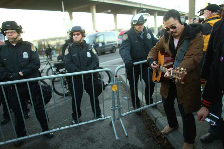 A protester plays his guitar near a police line on Monday, December 12, 2011 at the Port of Seattle. Hundreds of anti-Wall Street protesters gathered at the port and tried to shut down operations. Protesters scuffled with police during the rally and police used pepper spray and two flash-bang grenades to disperse the crowd after a protester threw a lit road flare toward officers. Another threw red paint on officers. Photo: JOSHUA TRUJILLO / SEATTLEPI.COM