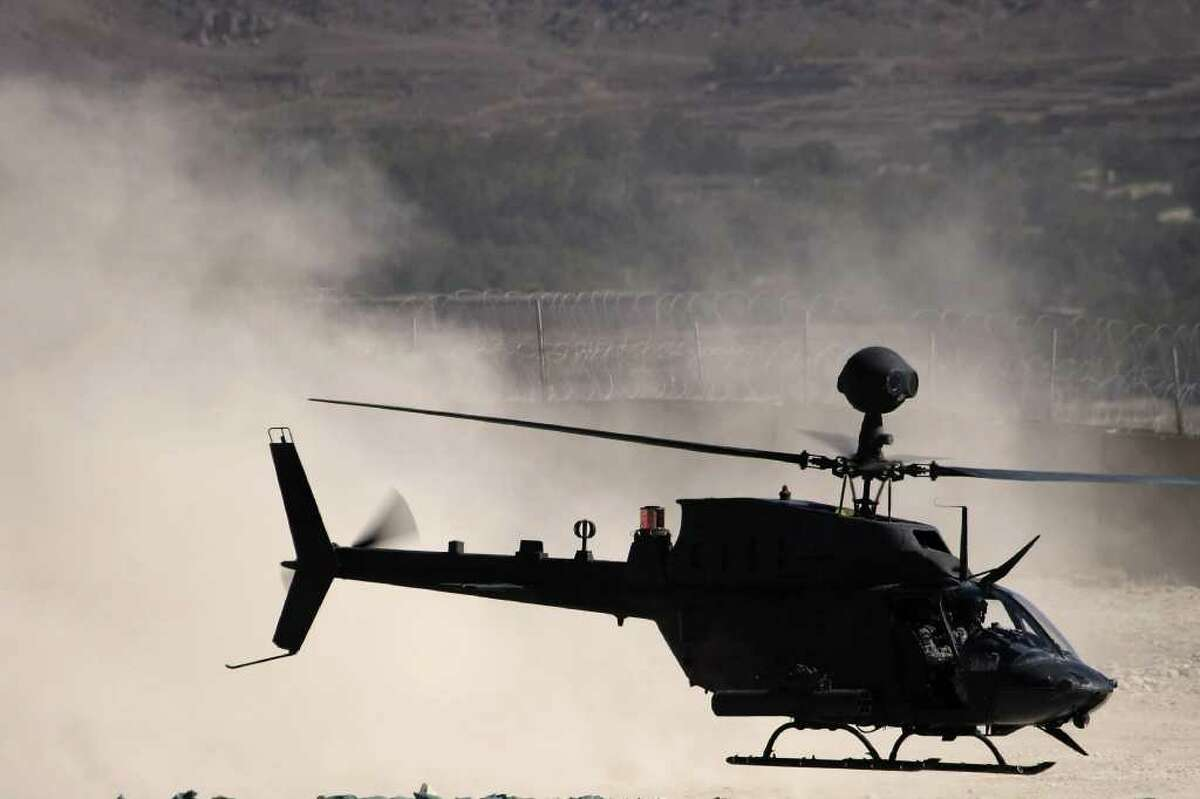 A US Army OH-58 Kiowa helicopter -- the same model as two helicopters involved in a fatal crash Monday night at Joint Base Lewis-McChord -- kicks up a cloud of dust in Afghanistan.