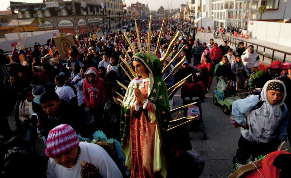 A pilgrim carries a statue of the Virgin of Guadalupe to the Basilica of Guadalupe in Mexico City, Monday Dec. 12, 2011. Thousands of people from all over the country converge on the basilica bringing images to be blessed on the feast day of the Virgin of Guadalupe. (AP Photo/Eduardo Verdugo)