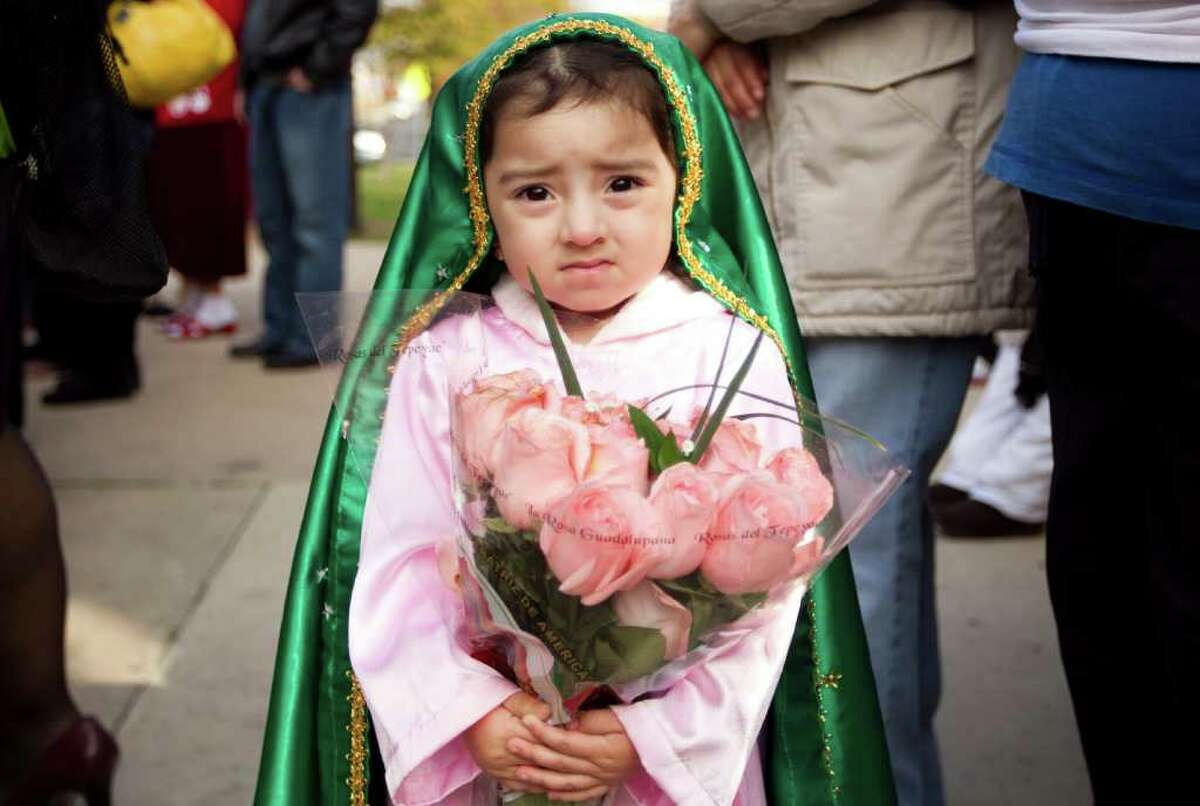 Brisa Escobedo, 2, carries roses at the Feast of Our Lady of Guadalupe at Our Lady of Guadalupe Catholic Church in Austin, Texas, on Monday Dec. 12, 2011. Dozens of parishioners walked in a procession four miles to the church for dancing and a Mass in honor of the Virgin of Guadalupe. (AP Photo/Austin American-Statesman, Jay Janner)