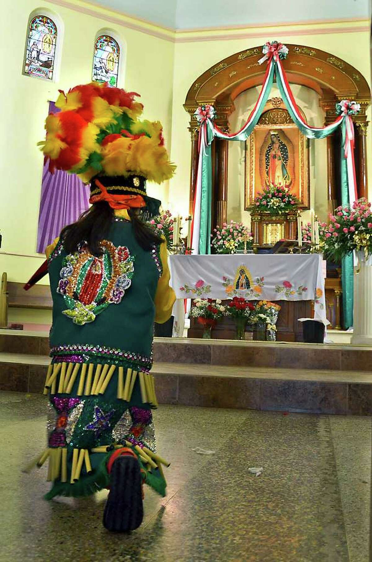 A member of the Matlachines from Our Lady of Guadalupe School performs in front of the altar during the Noon Mass at Our Lady of Guadalupe Catholic Church Monday. The Mass was celebrated to commemorate the 480th anniversary of the apparition by La Virgen to Juan Diego.
