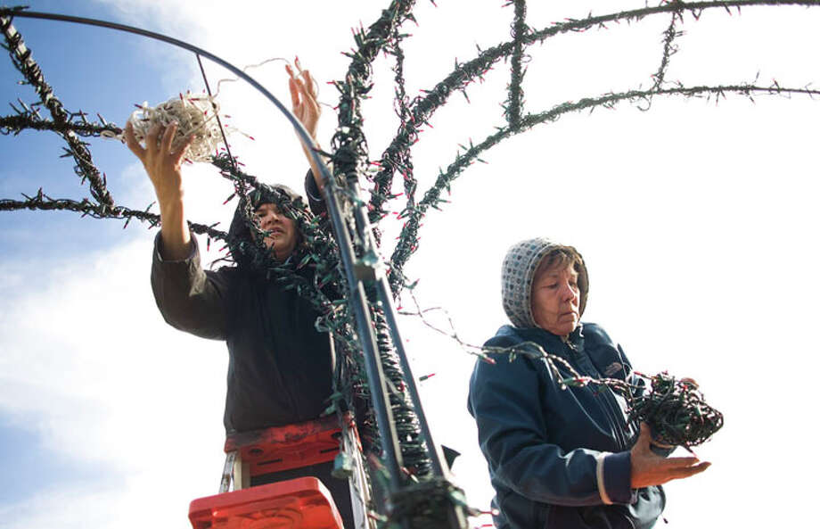 Kelly West AMERICAN-STATESMAN Anita Rodriguez, left, and Kelly Alexander remove holiday lights from the archway to the deck at Mozart's coffee shop on Lake Austin Blvd Wednesday, January 5, 2011. Alexander said it took about two weeks to put up all the lights, but only about three days to take them down. TEXMAS Photo: Kelly West, Austin American-Statesman / Austin American-Statesman