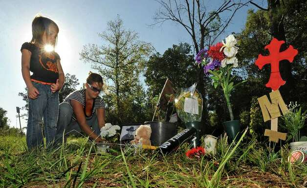 Danielle Dial and Sophie Daville, 4, place flowers at a memorial for Matt Thomas on Monday. Thomas was struck and killed by a train early Sunday morning. Photo taken Monday, October 17, 2011. Guiseppe Barranco/The Enterprise