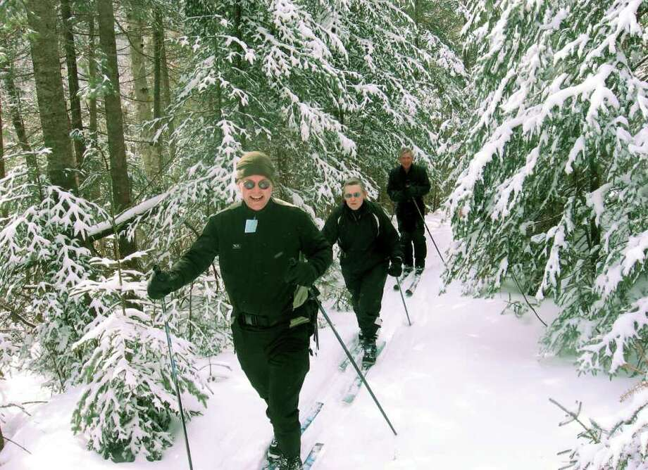 Fred Andersen, rear, guides Norma and Stewart Schwab of Ithaca on trails near Garnet Hill Cross Country Ski Center. The tour teaches skiers about the historic nature of the hills near North Creek. (Alan Wechsler / Times Union) Photo: ALL / times union