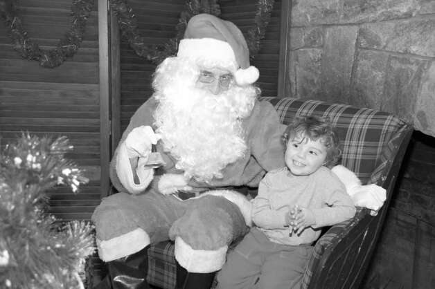 Santa Claus listens to the Christmas wishes of Marley Caron-Richman at the recent Round Hill Community Church Christmas Fair. Photo: Contributed Photo
