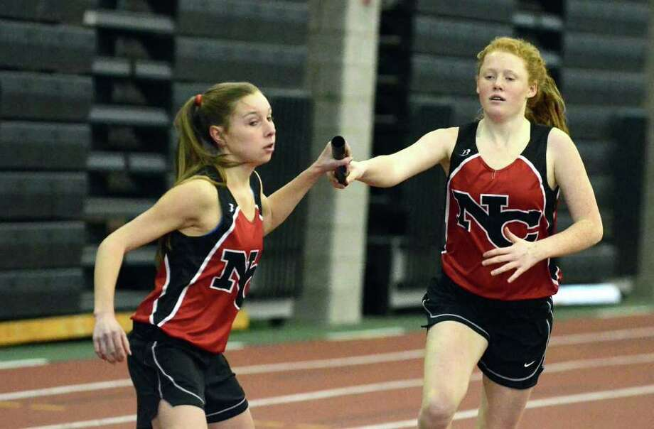 New Canaan's Emily Wood makes the hand off to Steph Benko in the 4x800 relay during the girls FCIAC championship track meet at New Haven Athletic Center on Thursday, Feb. 3, 2011. Photo: Amy Mortensen, ST / Connecticut Post Freelance