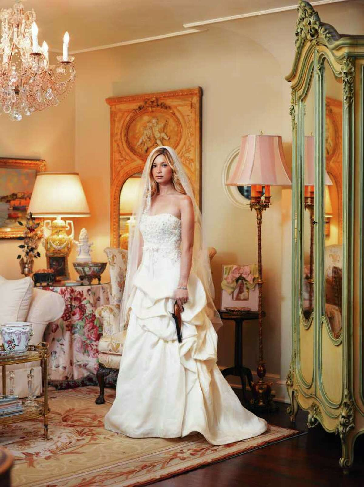 Jenevieve Pitman Zoch of San Antonio is pictured twice in McCrum's book. Here she dons her wedding dress while holding an antique pistol that's been in her family for generations.