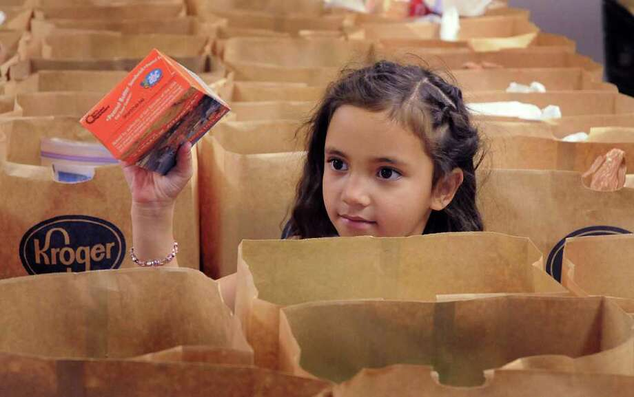 DAVID HOPPER: FOR THE CHRONICLE FILLING 'EM UP: Five-year-old Sydney Sudeth of The Woodlands fills a food sack at the Interfaith of The Woodlands Food Pantry. Photo: David Hopper / freelance