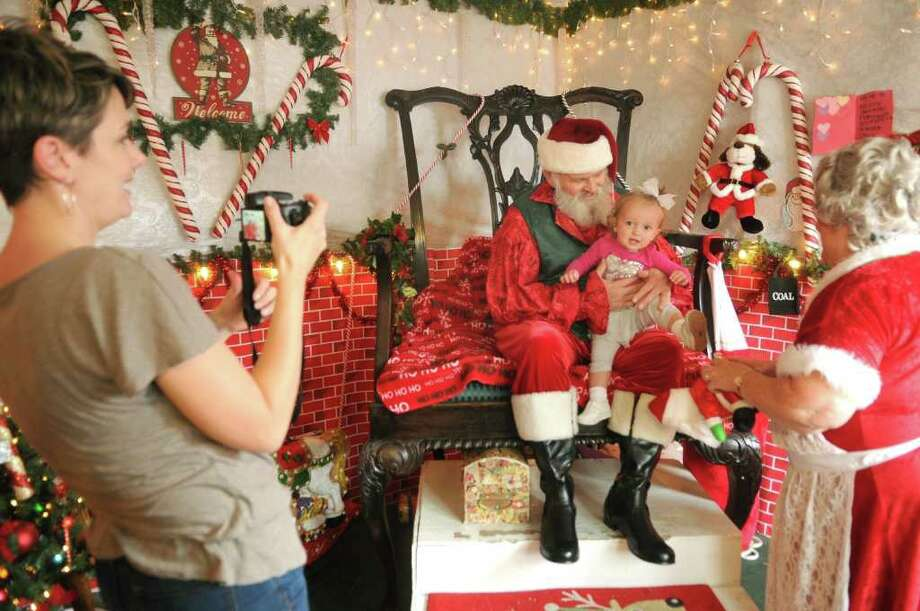 JERRY BAKER: FOR THE CHRONICLE SITTING WITH SANTA: Macy Lalonde visits with Santa while her mom, Elizabeth, left, snaps a photo during their visit to Santa's Village at the 31st Annual Home for the Holidays Celebration in Old Town Spring. Photo: Jerry Baker