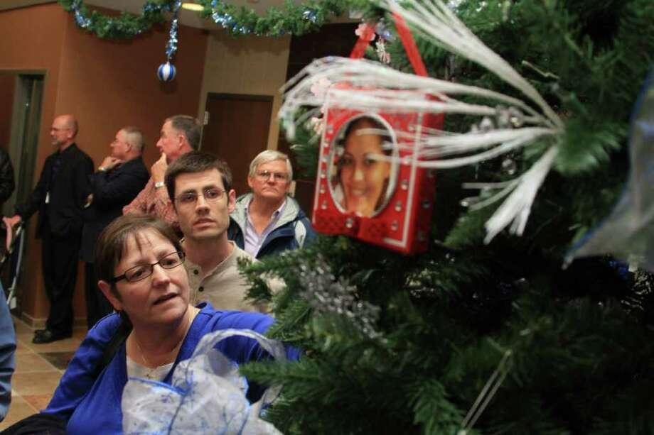 NOT FORGOTTEN: Kathy Cross of Clear Lake places an ornament on the Crime Victims' Tree while her son, Matthew, also of Clear Lake, watches. The ornament was in honor of her nephew, Joshua Wilkerson, who was murdered in 2010. Photo: Christy Wooten / freelance