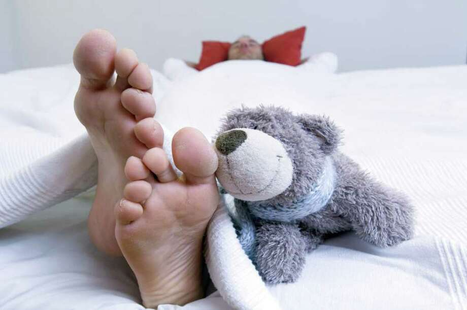 Man sleeping in bed, barefoot and teddy bear in foreground Photo: Alain Schroeder / Onoky / Photon / onoky - Fotolia