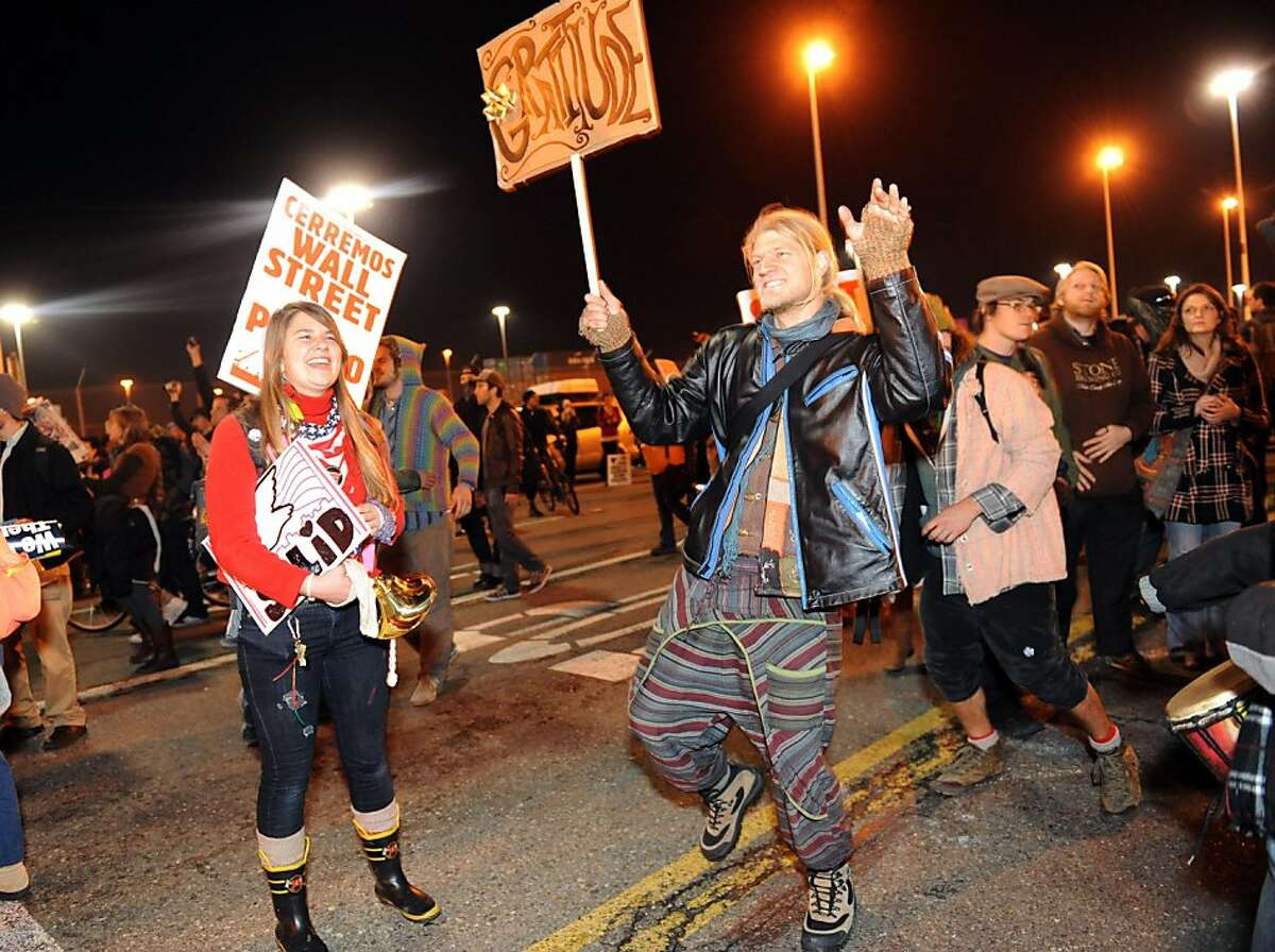 Philip Oeaoje dances along with other protesters at the Port of Oakland on Monday, Dec. 12, 2011, in Oakland, Calif.
