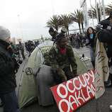Melvin Kelley of Oakland places an Occupy Oakland sign in front of a tent after marching with others from Tactical Action Committee to join other protesters in front of the entrance to Berths 55 and 56 at the Port of Oakland on Monday, December 12, 2011 in Oakland, Calif. Almost half the berths at the Port of Oakland have temporarily ceased operations Monday after hundreds of protesters spent the morning blocking intersections in the port.