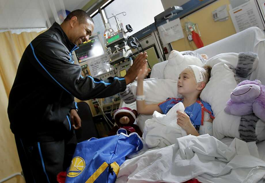 Coach Mark Jackson got a nice greeting from Elissa Loock, 9 years, from Lodi, Calif. New Golden State Warriors coach Mark Jackson and forward Dorell Wright payed a visit to the pediatric oncology unit at the Kaiser Permanente  Medical Center in Oakland Calif. Monday December 12, 2011. Photo: Brant Ward, The Chronicle