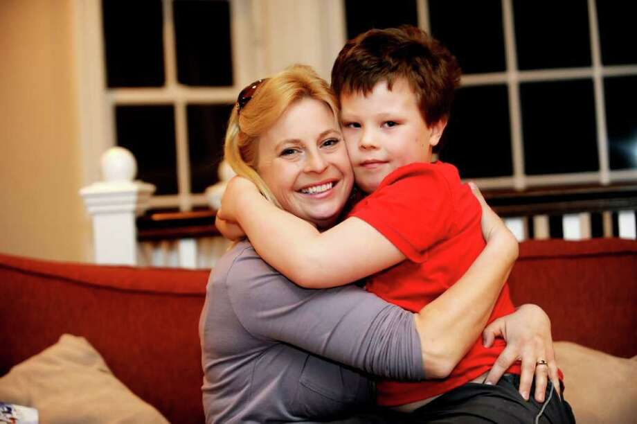 Ellen Currie gives her son, Daniel, 7, a hug in their home in Old Greenwich Monday, Dec. 12, 2011. Daniel is autistic. Photo: Helen Neafsey / Greenwich Time