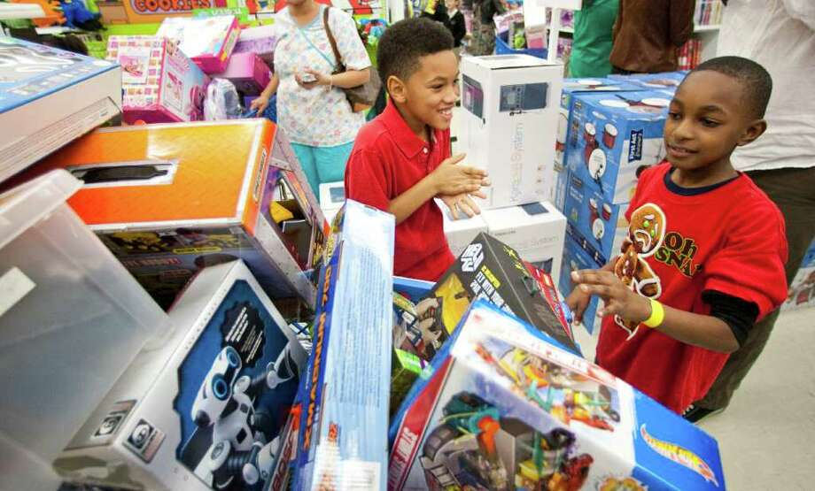 Devage Williams, 10, left, can't believe his eyes when he sees what his cousin Alex Edwards, 9, selected when Alex participated in AJ's Shopping Spree, by Houston Texans wide receiver Andre Johnson,Tuesday, Dec. 13, 2011, in Toys R' Us in Houston. The boys call each other brothers because Alex is living with his cousin's family. Eleven kids, selected by Child Protective Services, had 80 seconds to get all the toys they could and when time was up Johnson payed the bill. Photo: Nick De La Torre, Houston Chronicle / © 2011  Houston Chronicle